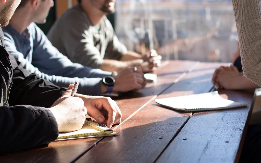Mehrere Personen um einen Konferenztisch